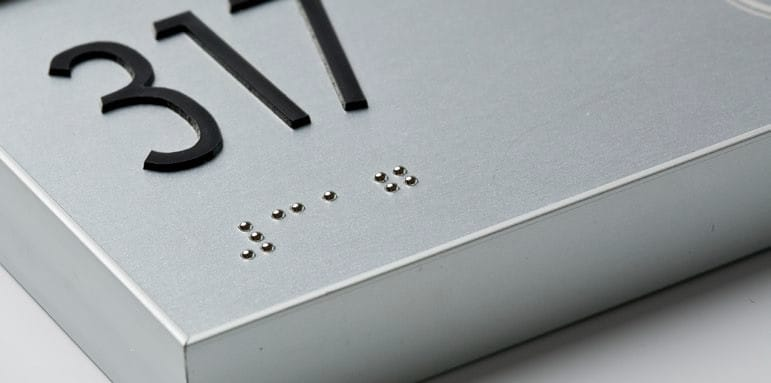 ADA signage of room number 317 with a close up of the Braille.