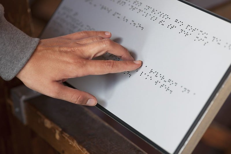 Person touching a braille directory.